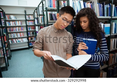 Portrait of a young students reading book in library  - stock photo