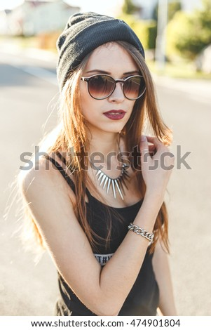 portrait of a young stylish hipster girl dressed in a cap and sunglasses
