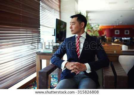 Portrait of a young successful asian businessman thinking about something while sitting in modern office interior space, thoughtful men entrepreneur resting after conference or meeting with partners - stock photo