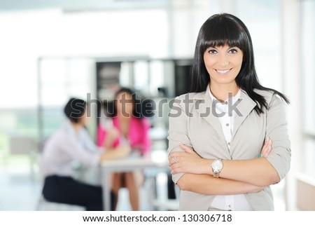 Portrait of a young successful business woman with working team at office - stock photo