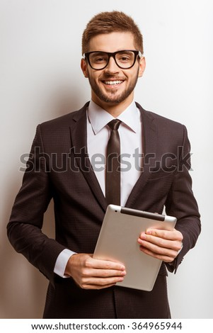 Portrait of a young successful businessman in a business suit, using the tablet on gray background - stock photo