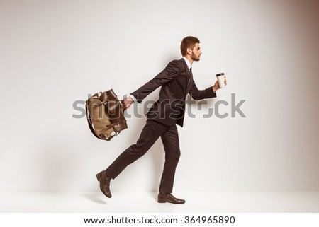 Portrait of a young successful businessman in a business suit with a bag and coffee in hands on a gray background - stock photo