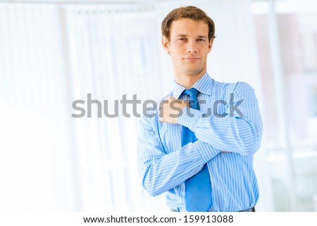 Portrait of a young successful businessman in the office, rubbing his chin