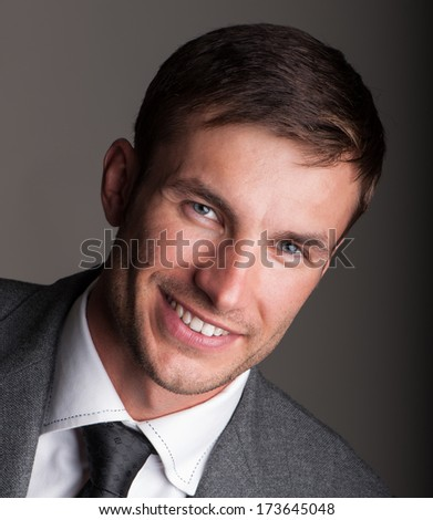 Portrait of a young successful businessman on a gray background in studio - stock photo