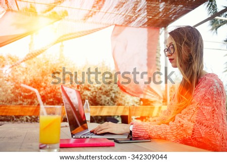 Portrait of a young successful female freelancer using net-book for distance work during morning breakfast, attractive woman keyboarding on laptop computer while sitting in sidewalk cafe in summer day - stock photo