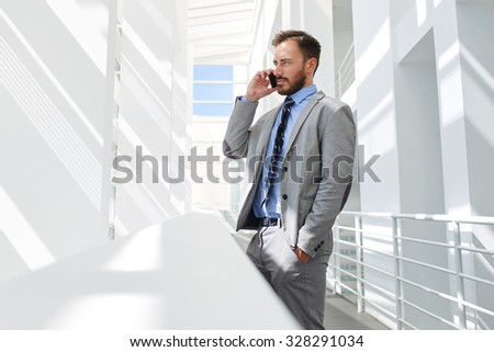 Portrait of a young successful man ceo talking on mobile phone while standing in modern office interior, confident male managing director having telephone conversation while resting after briefing  - stock photo
