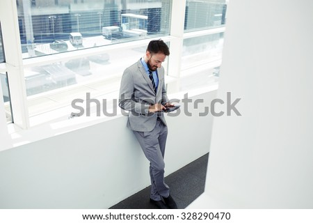 Portrait of a young successful manager using touch pad to prepare for working day while standing in office space, purposeful business man or economist reading news on digital tablet during work break - stock photo