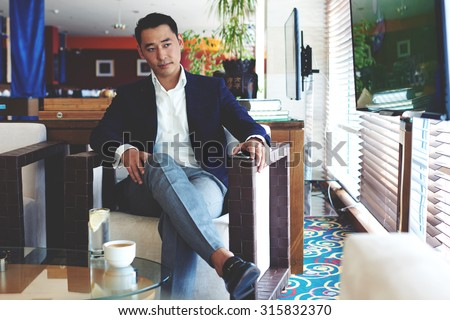 Portrait of a young successful managing director watching news on TV while waiting for business partners in modern restaurant, confident intelligent business men relaxing in cafe during lunch break - stock photo