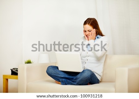 Portrait of a young surprised woman working on sofa