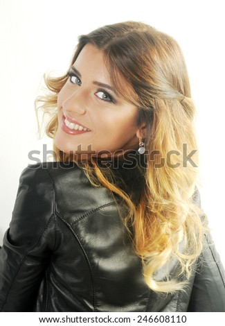 portrait of a Young teen girl leaning towards the White wall with her back towards the camera and looking over her shoulder smiling at the camera isolated on white - stock photo