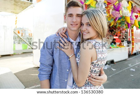 Portrait of a young teenage couple hugging while enjoying together being in a funfair ground with games and toy prices in the background, smiling. - stock photo