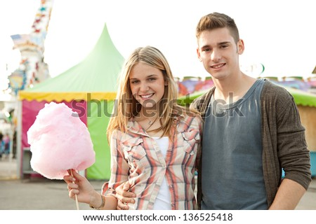 Portrait of a young teenage couple walking and eating cotton candy floss while enjoying visiting a funfair ground with rides in the background, smiling. - stock photo