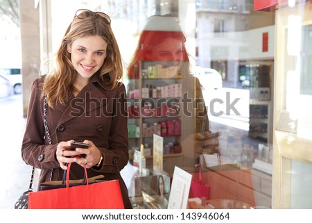 Portrait of a young teenager tourist visiting the city and carrying paper shopping bags while leaning on a fashion store window, using her smartphone device and smiling. - stock photo