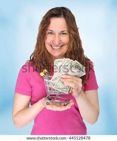 Portrait of a young thoughtful woman with mini shopping cart with money                   - stock photo