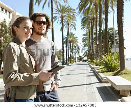 Portrait of a young tourist couple on vacation in a destination city palm trees boulevard, holding a technology tablet during a sunny day.