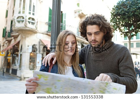 Portrait of a young tourist couple visiting a destination city and reading a street map while on vacation in Europe. - stock photo