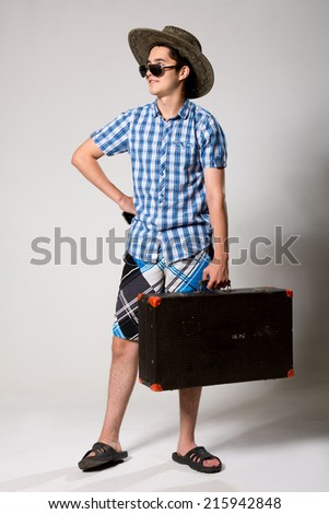 Portrait of a young tourist in a full-length looking away. A man with a suitcase with sunglasses and hat - stock photo
