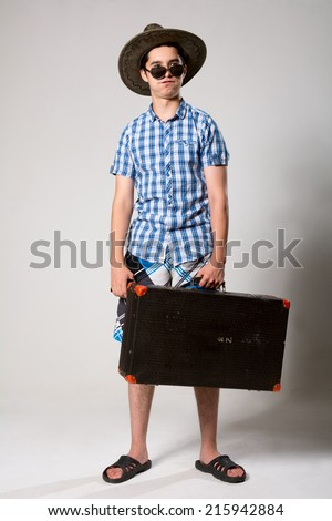 Portrait of a young tourist in a full-length looking away. Tired man with a suitcase with sunglasses and hat - stock photo