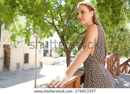 Portrait of a young tourist woman leaning on a wooden banister balcony in a leafy street on holiday, smiling, exterior. Travel and lifestyle summer vacation, outdoors park. Smart woman, lifestyle.