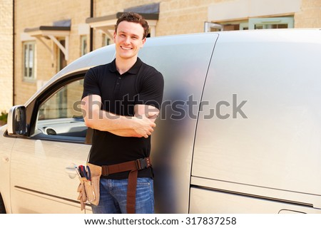 Portrait of a young tradesman by his van - stock photo