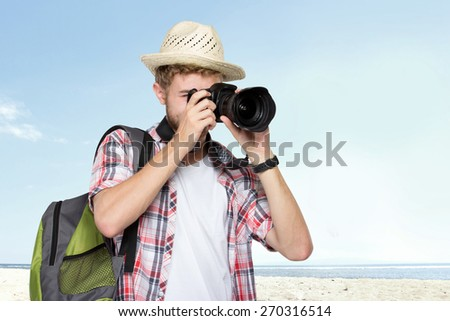 portrait of a young traveling man with backpack taking a picture - stock photo