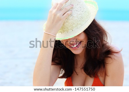 Portrait of a young trendy woman in hat having fun on the beach - stock photo