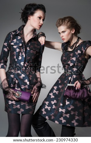 portrait of a young two woman with a purse posing - stock photo