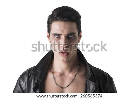 Portrait of a Young Vampire Man in an Open Black Leather Jacket, Looking at the Camera, on a White Background. - stock photo