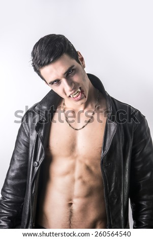 Portrait of a Young Vampire Man in an Open Black Leather Jacket, Showing his Chest and Abs, Looking at the Camera, on a White Background. - stock photo