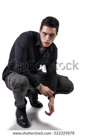 Portrait of a Young Vampire Man with Black Shirt Sitting on Floor with Hands Joined, Isolated on White