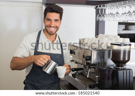 Portrait of a young waiter smiling and making cup of coffee at coffee shop - stock photo