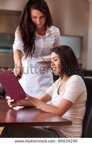 Portrait of a young waitress advising a customer pointing something on the menu - stock photo
