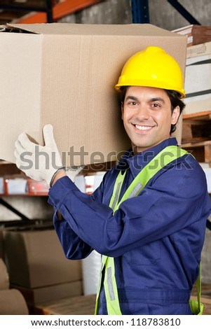 Portrait of a young warehouse worker carrying cardboard box - stock photo
