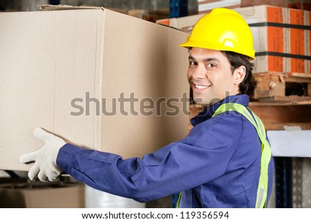 Portrait of a young warehouse worker lifting cardboard box - stock photo