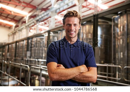 Portrait of a young white man working at a wine factory