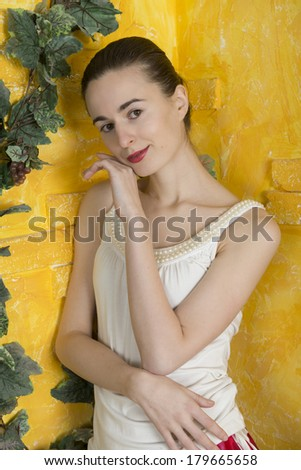 Portrait of a young woman against a background of yellow village house