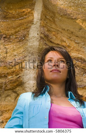 Portrait of a young woman against a rocky background. - stock photo
