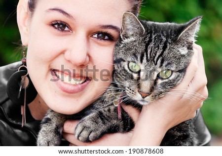 Portrait of a young woman and her tabby cat. - stock photo