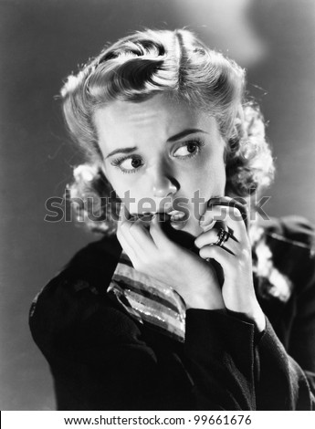 Portrait of a young woman biting her nail and looking frightened