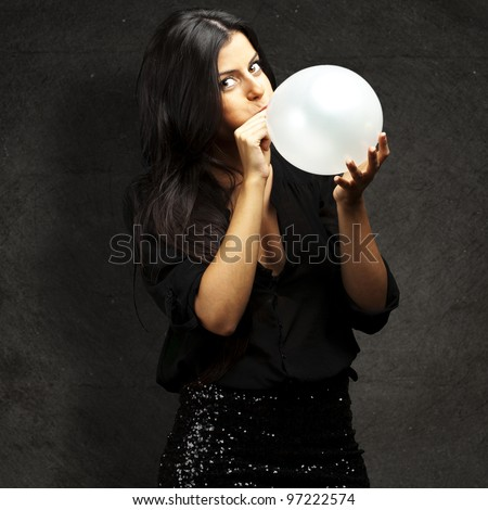 portrait of a young woman blowing up a balloon against a grunge wall