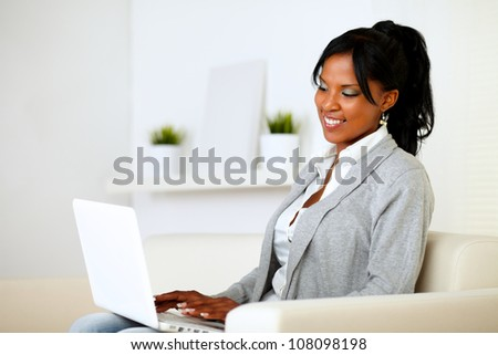 Portrait of a young woman browsing the Internet on laptop while is sitting on sofa at home - stock photo