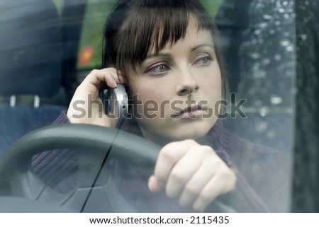 portrait of a young woman, brunette in a car making a phonecall-close up