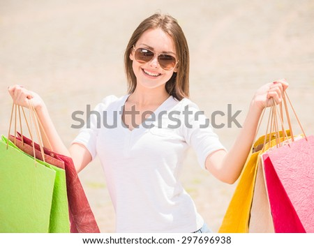 Portrait of a young woman carrying many paper shopping bags and smiling.