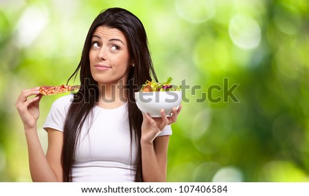 portrait of a young woman choosing pizza or salad against a nature background