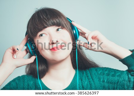 Portrait of a young woman corrects headphones, isolated on a gray background