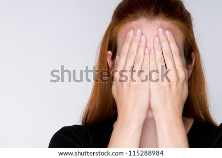 Portrait of a  young woman covering face with hands
