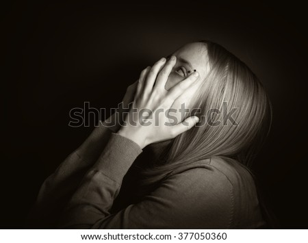 Portrait of a young woman covering face with hands in mysterious light