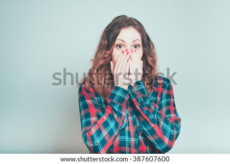 Portrait of a young woman covers her mouth with her hands isolated on a gray background - stock photo