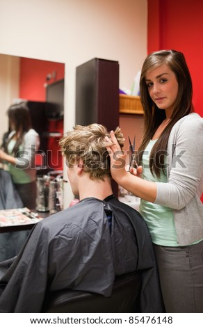 Portrait of a young woman cutting a man's hair with scissors - stock photo