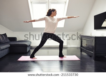 Portrait of a young woman doing yoga on an exercising mat in her living room. Caucasian female model in warrior pose. - stock photo